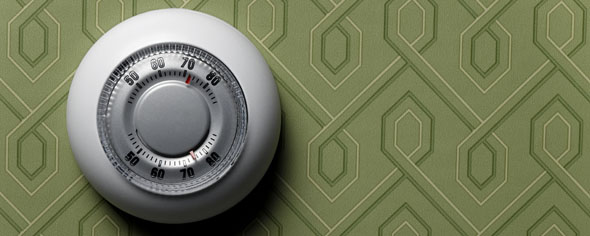 Thermostat on green wallpapered wall, close-up